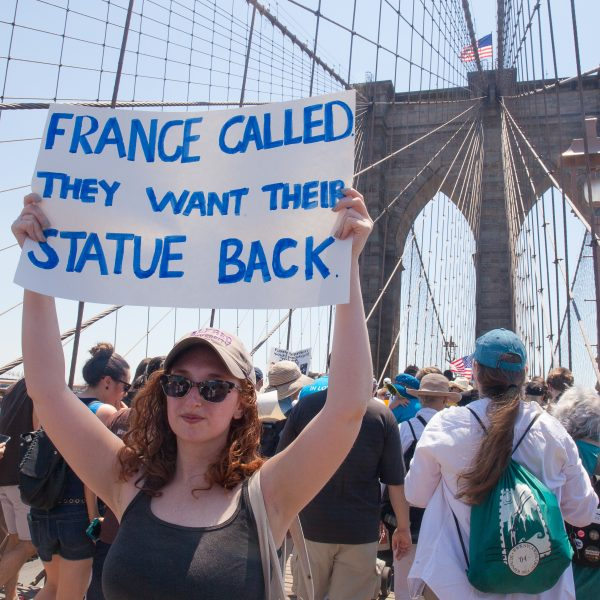 "6/30/2018. New York City - March: ""Families Belong Together."" Woman with a sign that reads: ""France called. They want their statue (Statue of Liberty) back."" People crossing the Brooklyn Bridge in support of refugee families. People's protectors are marching from Foley Square in Manhattan to Cadman Plaza in Brooklyn. Credit: Photo by Javier Soriano/LoveIsAmor.com"