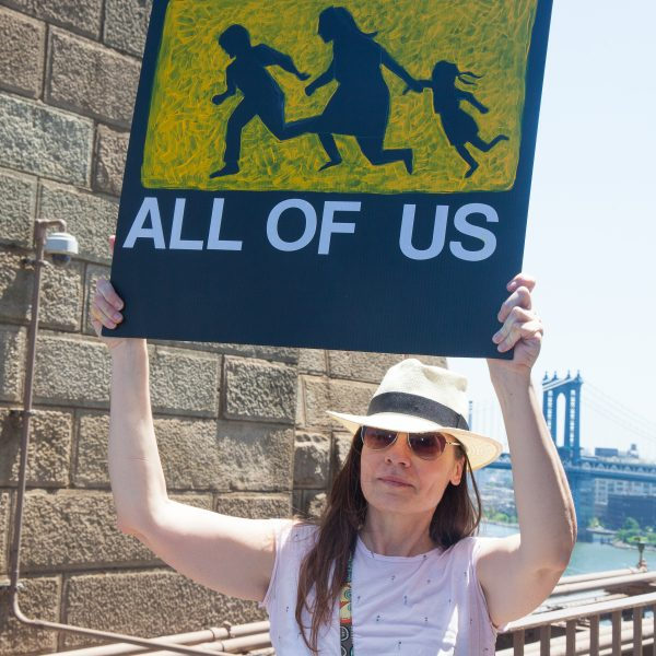 "6/30/2018. New York City - March: ""Families Belong Together."" A woman with a sign that reads: ""This is all of us."" People crossing the Brooklyn Bridge in support of refugee families. People's protectors are marching from Foley Square in Manhattan to Cadman Plaza in Brooklyn. Credit: Photo by Javier Soriano/LoveIsAmor.com"