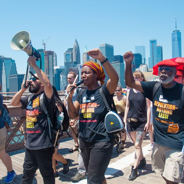 "6/30/2018. New York City - March: ""Families Belong Together."" People wearing t-shirts that reads: 'Revolution -nothing less!"" People crossing the Brooklyn Bridge in support of refugee families. People's protectors are marching from Foley Square in Manhattan to Cadman Plaza in Brooklyn. Credit: Photo by Javier Soriano/LoveIsAmor.com"