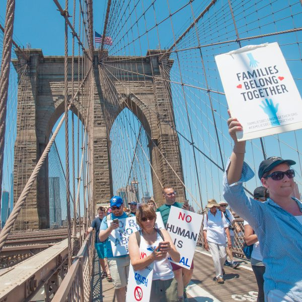 "6/30/2018. New York City - March: ""Families Belong Together."" Woman with a sign that reads: ""Families belong together."" People crossing the Brooklyn Bridge in support of refugee families. People's protectors are marching from Foley Square in Manhattan to Cadman Plaza in Brooklyn. Credit: Photo by Javier Soriano/LoveIsAmor.com"