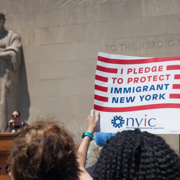 "6/30/2018. New York City - March: ""Families Belong Together."" Woman with a sign that reads: ""I pledge to protect immigrant New York. NYIC/New York Immigration Coalition."" People at Cadman Plaza in support of refugee families. People's protectors marched from Foley Square in Manhattan to Cadman Plaza in Brooklyn. Photo by Javier Soriano/LoveIsAmor.com"