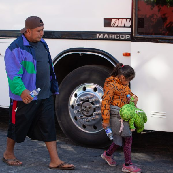 "Tlaquepaque, Guadalajara. Jalisco, Mexico. Monday, November 19th, 2018. A refugee father and his child boarding a bus to Sinaloa. Hundreds of refugees fleeing violence and extreme poverty in Central America have been staying at ""El Refugio. Casa del Migrante"" for one or two days. These refugees are part of the second caravan. They want to apply for asylum in the United States of America. Credit: Photo by LoveIsAmor.com"