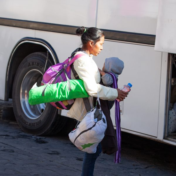 "Tlaquepaque, Guadalajara. Jalisco, Mexico. Monday, November 19th, 2018. A refugee mother and her baby boarding a bus to Sinaloa. Hundreds of refugees fleeing violence and extreme poverty in Central America have been staying at ""El Refugio. Casa del Migrante"" for one or two days. This immigrant family is part of the second caravan. They want to apply for asylum in the United States of America. Credit: Photo by LoveIsAmor.com"