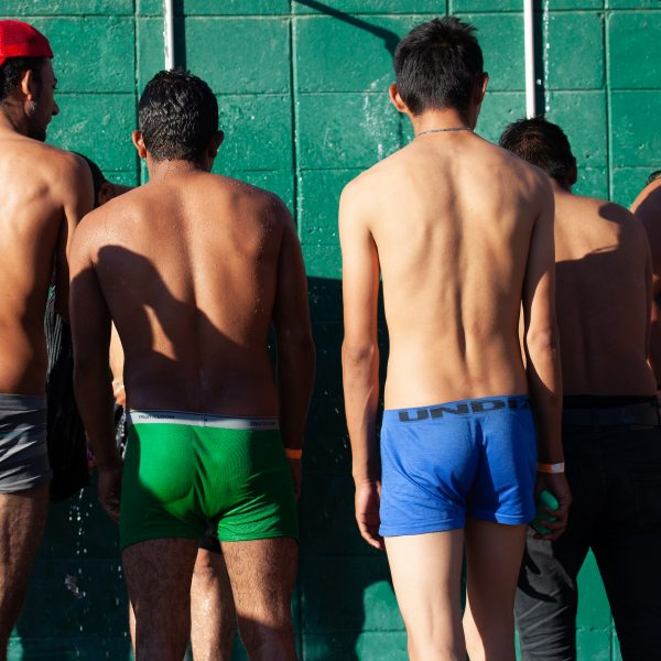 Tijuana, Baja California. Mexico. Monday, November 26th, 2018. A group of refugee men taking a shower at Unidad Deportiva Benito Juárez (an improvised shelter for the caravans of immigrants). They are fleeing violence and extreme poverty in their countries in Central America. They want to apply for asylum in the United States of America. Credit: Photo by LoveIsAmor.com