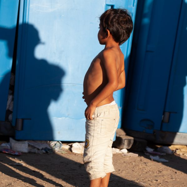Tijuana, Baja California. Mexico. Monday, November 26th, 2018. A refugee boy looking for a bathroom at Unidad Deportiva Benito Juárez (an improvised shelter for the caravans of immigrants). Bathrooms are located inside the makeshift shelter. Bathrooms smell really bad and are already at their maximum capacity. Authorities need to change the portable toilets. This is not healthy for refugees, volunteers, media and others. Immigrants are fleeing violence and extreme poverty in their countries in Central America. They want to apply for asylum in the United States of America. Credit: Photo by LoveIsAmor.com