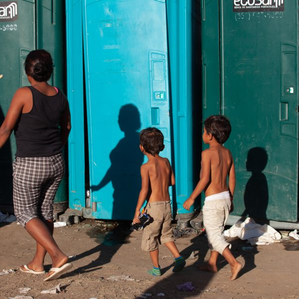 Tijuana, Baja California. Mexico. Monday, November 26th, 2018. A family of refugee looking for a bathroom at Unidad Deportiva Benito Juárez (an improvised shelter for the caravans of immigrants). Bathrooms are located inside the makeshift shelter. Bathrooms smell really bad and are already at their maximum capacity. Authorities need to change the portable toilets. This is not healthy for refugees, volunteers, media and others. Immigrants are fleeing violence and extreme poverty in their countries in Central America. They want to apply for asylum in the United States of America. Credit: Photo by LoveIsAmor.com