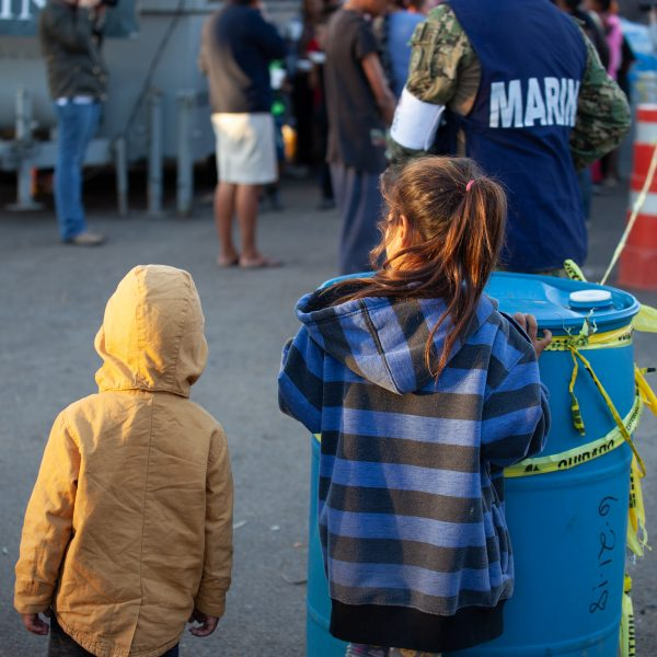 Tijuana, Baja California. Mexico. Monday, November 26th, 2018. Children and their parents waiting in line to get food. Mexican Marina is giving food to refugees staying at Unidad Deportiva Benito Juárez (an improvised shelter for the caravans of immigrants). Refugees are fleeing violence and extreme poverty in their countries in Central America. They want to apply for asylum in the United States of America. Credit: Photo by LoveIsAmor.com