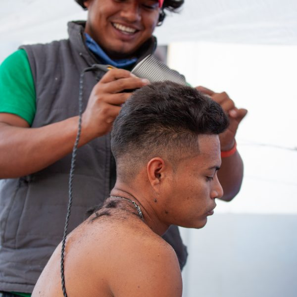 Tijuana, Baja California. Mexico. Tuesday, November 27th, 2018. A refugee man getting a haircut by another refugee man at Unidad Deportiva Benito Juárez (an improvised shelter for the caravans of immigrants). Refugees are fleeing violence in their countries in Central America. They want to apply for asylum in the United States of America. Credit: Photo by LoveIsAmor.com