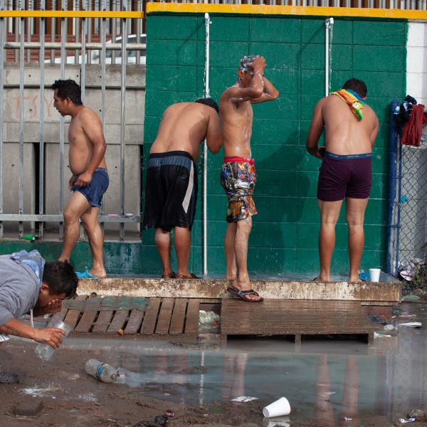 Tijuana, Baja California. Mexico. Thursday, November 29th, 2018. Refugee men taking a shower at Unidad Deportiva Benito Juárez (an improvised shelter for the caravans of immigrants). Refugees are fleeing violence and extreme poverty in their countries in Central America. They want to apply for asylum in the United States of America. They were told they have to wait more than a month to apply for asylum. Credit: Photo by LoveIsAmor.com