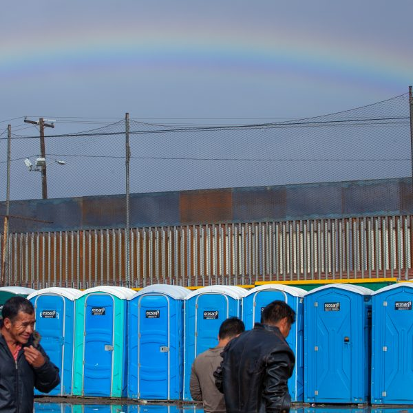Tijuana, Baja California. Mexico. Thursday, November 29th, 2018. It was raining last night and it was raining all day today. Refugees in front of portable toilets and the rainbow in the sky. They are staying at Unidad Deportiva Benito Juárez (an improvised shelter for the caravans of immigrants). Refugees are fleeing violence in their countries in Central America. They want to apply for asylum in the United States of America. Credit: Photo by LoveIsAmor.com
