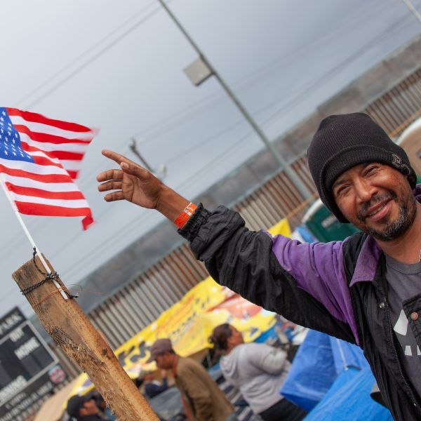 Tijuana, Baja California. Mexico. Thursday, November 29th, 2018. Refugee man from Honduras with the American flag at Unidad Deportiva Benito Juárez (an improvised shelter for the caravans of immigrants). Refugees are fleeing violence in their countries in Central America. They want to apply for asylum in the United States of America. They were told they have to wait more than a month to apply for asylum. Credit: Photo by LoveIsAmor.com